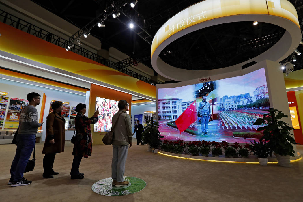 Visitors watch a man appearing on a screen as he experiences a national anthem flag raising ceremony on Monday, Oct. 23, 2017, at an exhibition highlighting China's achievements at the Beijing Exh ...