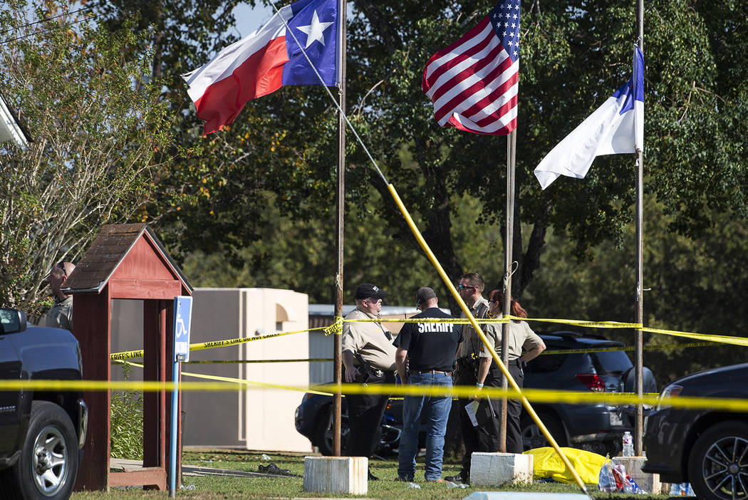Law enforcement officials stand next to a covered body at the scene of a fatal shooting at the First Baptist Church in Sutherland Springs, Texas, on Sunday, Nov. 5, 2017. (Nick Wagner/Austin Ameri ...