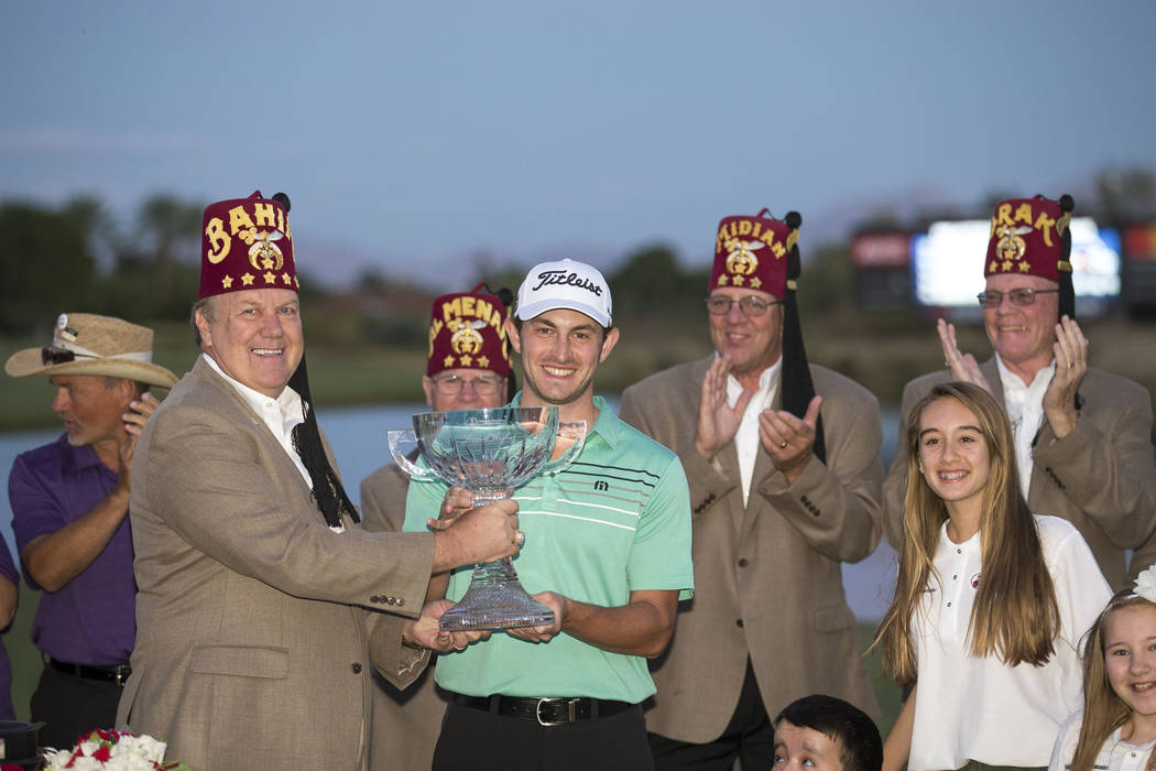 Professional golfer Patrick Cantlay, center, of California is presented with the trophy after winning the Shriners Hospitals For Children Open at TPC at Summerlin in Las Vegas, Sunday, Nov. 5, 201 ...