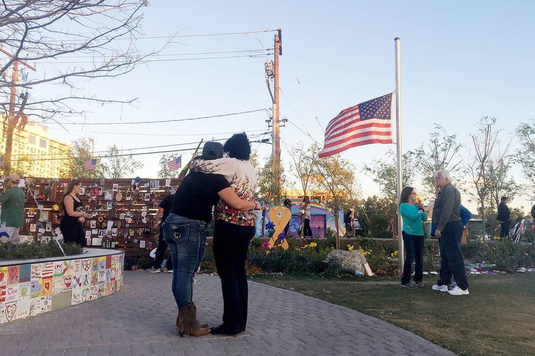 A Route 91 Harvest festival survivor is comforted as she traveled from California to visit Las Vegas for the first since the shooting, at the Las Vegas Community Healing Garden in Las Vegas, Sunda ...