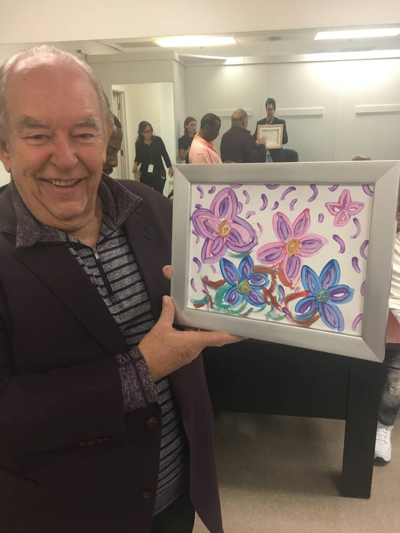 Robin Leach is shown with a painting by Britney Spears, which was put up for auction and sold to none other than Leach for $10,000. Leach is shown with his new painting backstage at The Venetian T ...