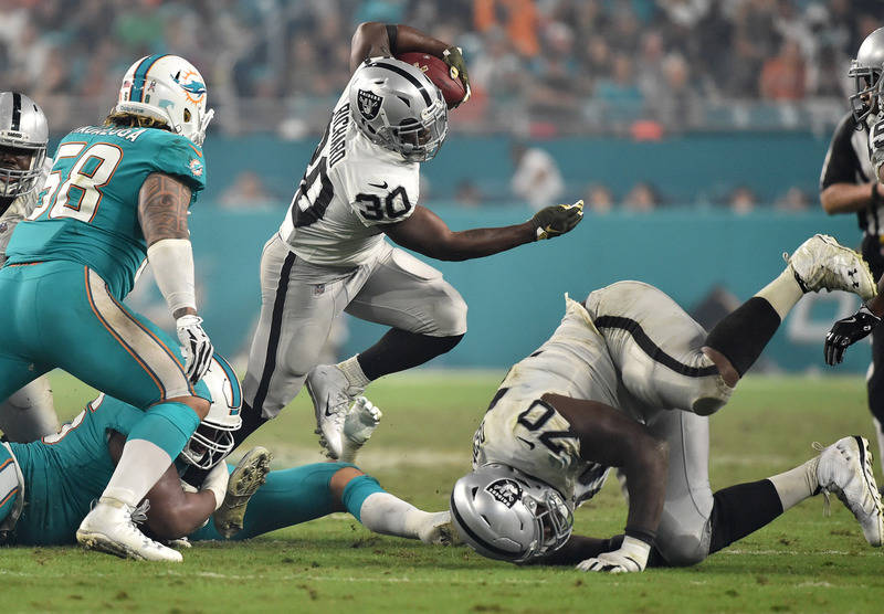 Nov 5, 2017; Miami Gardens, FL, USA; Oakland Raiders running back Jalen Richard (30) runs past Miami Dolphins defenders during the second half at Hard Rock Stadium. Mandatory Credit: Steve Mitchel ...