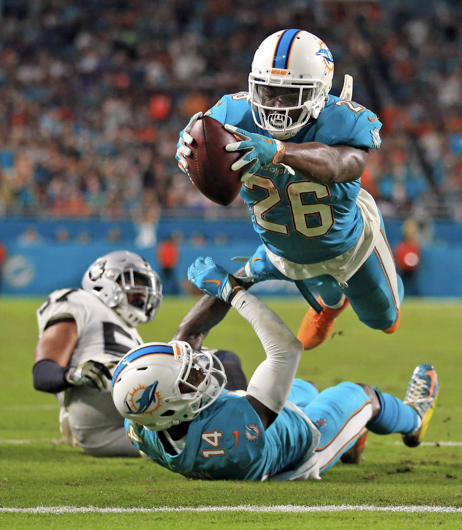 Miami Dolphins running back Damien Williams (26) dives over the goal line  to score a touchdown in the second quarter of an NFL football game against the Oakland Raiders, Sunday, Nov. 5, 2017, in  ...