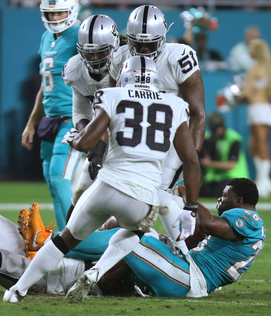 Miami Dolphins running back Damien Williams (26) has his helmet pulled off at the end of a run during the first half of the NFL game against the Oakland Raiders in Miami Gardens, Fla., Sunday, Nov ...