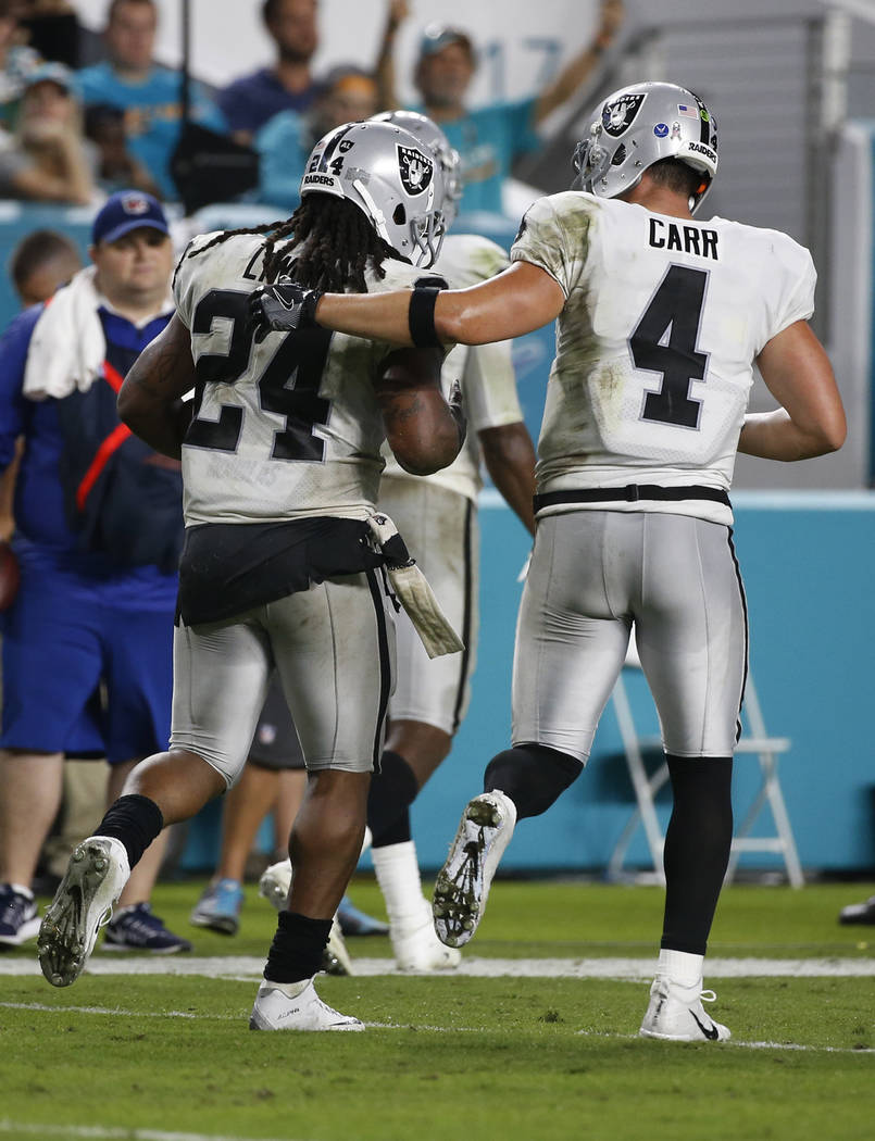 Oakland Raiders quarterback Derek Carr (4) congratulates running back Marshawn Lynch (24), after Lynch grabbed a touchdown pass, during the second half of an NFL football game against the Miami Do ...