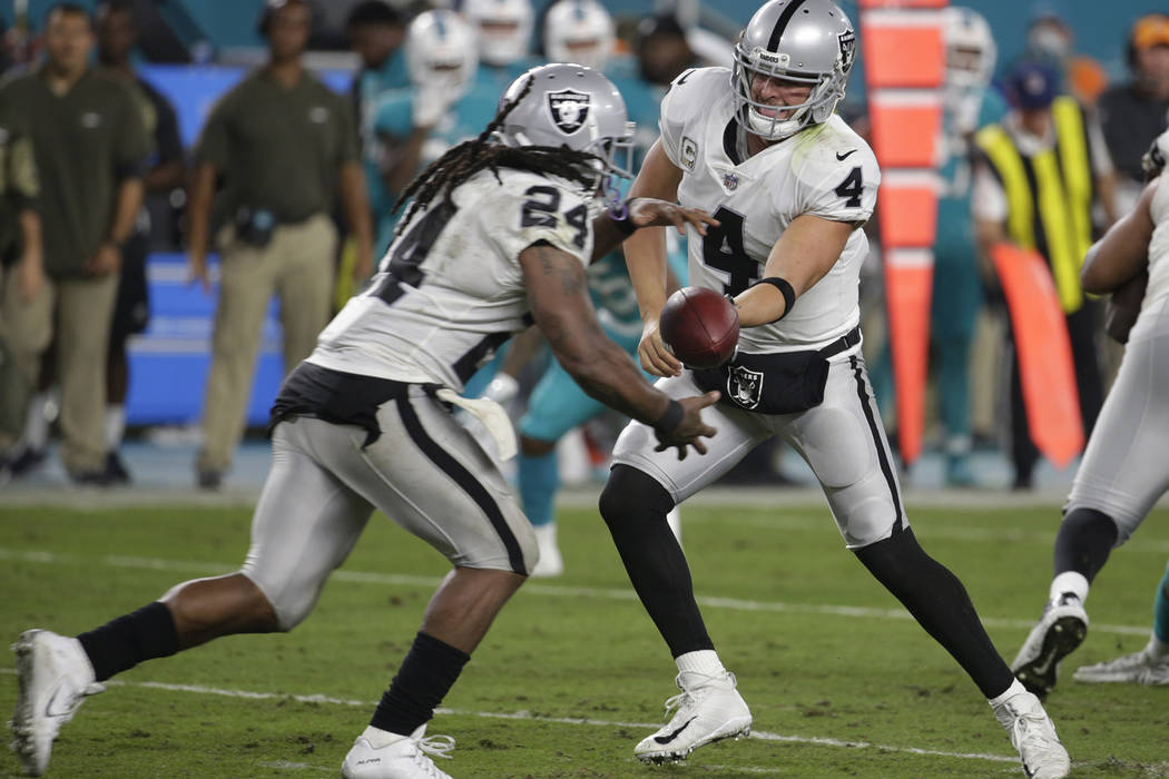 Oakland Raiders quarterback Derek Carr (4) hands the ball to running back Marshawn Lynch (24), during the first half of an NFL football game against the Miami Dolphins, Sunday, Nov. 5, 2017, in Mi ...
