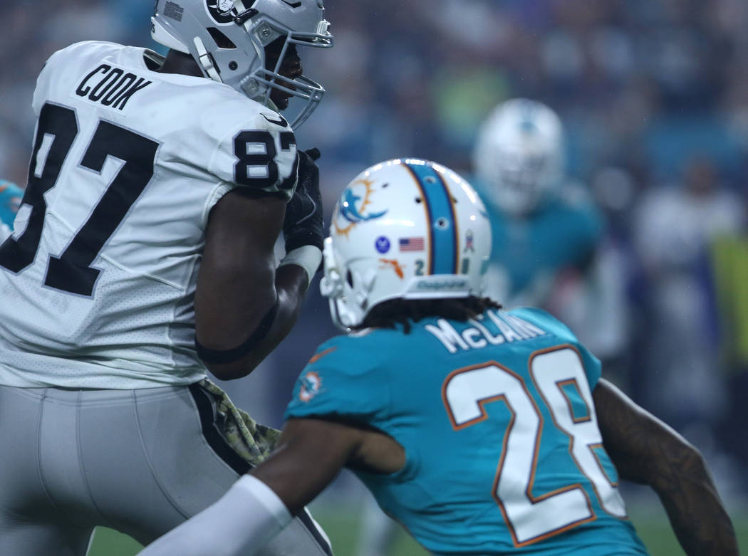 Oakland Raiders tight end Jared Cook (87) catches a pass as Miami Dolphins cornerback Bobby McCain (28) defends during the first half of the NFL game in Miami Gardens, Fla., Sunday, Nov. 5, 2017.  ...