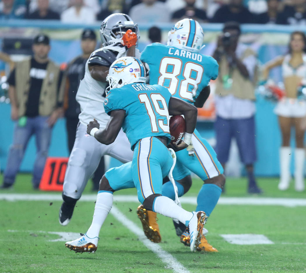 Miami Dolphins wide receiver Jakeem Grant (19) runs with the football on a kickoff return as wide receiver Leonte Carroo (88) holds off a defender during the first half of the NFL game against the ...