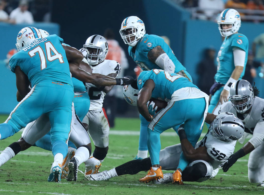 Miami Dolphins running back Damien Williams (26) is tackled by Oakland Raiders defensive end Khalil Mack (52) during the first half of the NFL game in Miami Gardens, Fla., Sunday, Nov. 5, 2017. He ...