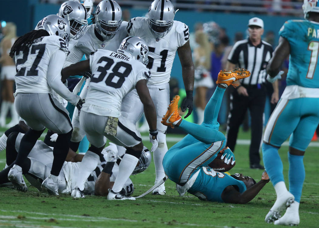 Miami Dolphins running back Damien Williams (26) is surrounded Oakland Raiders defenders during the first half of the NFL game against the Oakland Raiders in Miami Gardens, Fla., Sunday, Nov. 5, 2 ...