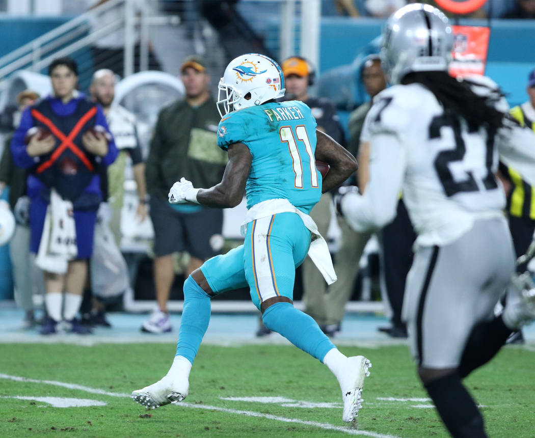 Miami Dolphins wide receiver DeVante Parker (11) runs after catching the football as Oakland Raiders free safety Reggie Nelson (27) pursues him during the first half of the NFL game in Miami Garde ...