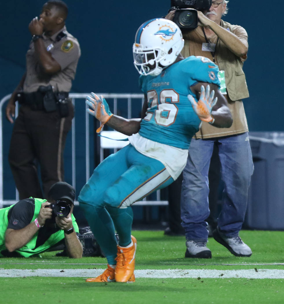 Miami Dolphins running back Damien Williams (26) celebrates a touchdown during the first half of the NFL game against the Oakland Raiders in Miami Gardens, Fla., Sunday, Nov. 5, 2017. Heidi Fang L ...
