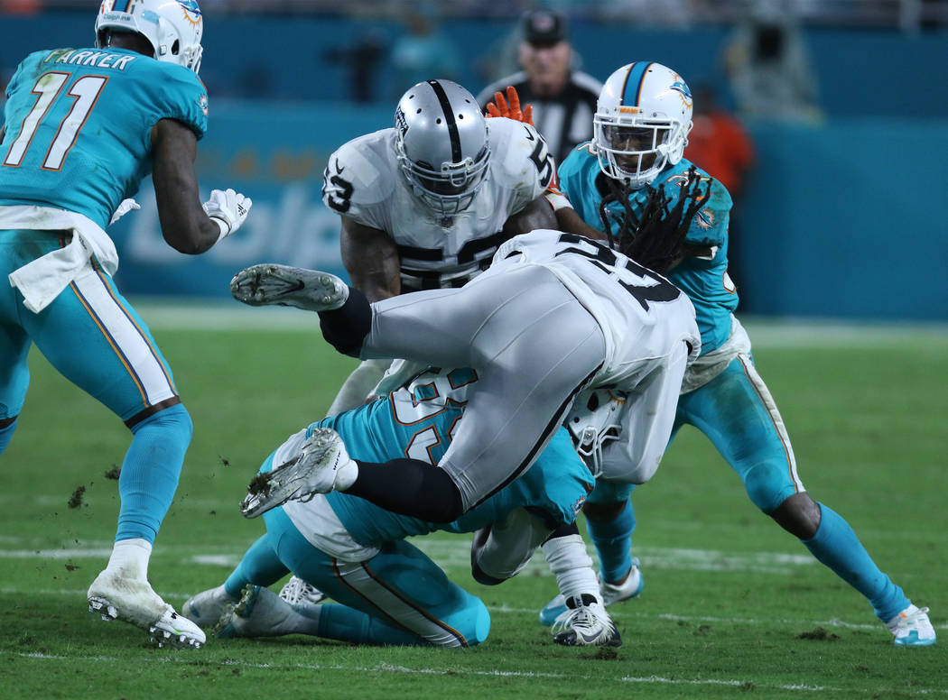 Oakland Raiders free safety Reggie Nelson (27) tackles Miami Dolphins tight end Julius Thomas (89) during the first half of the NFL game in Miami Gardens, Fla., Sunday, Nov. 5, 2017. Heidi Fang La ...