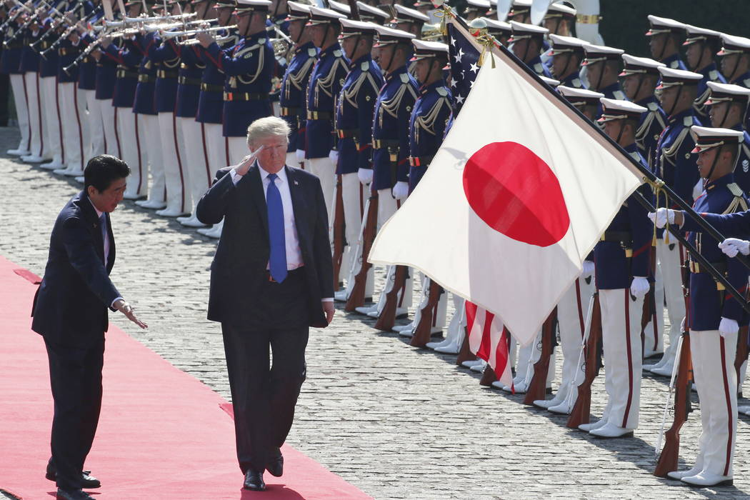 President Donald Trump reviews an honor guard during a welcome ceremony with Japanese Prime Minister Shinzo Abe, left, at Akasaka Palace in Tokyo, Monday, Nov. 6, 2017. (AP Photo/Koji Sasahara,pool)
