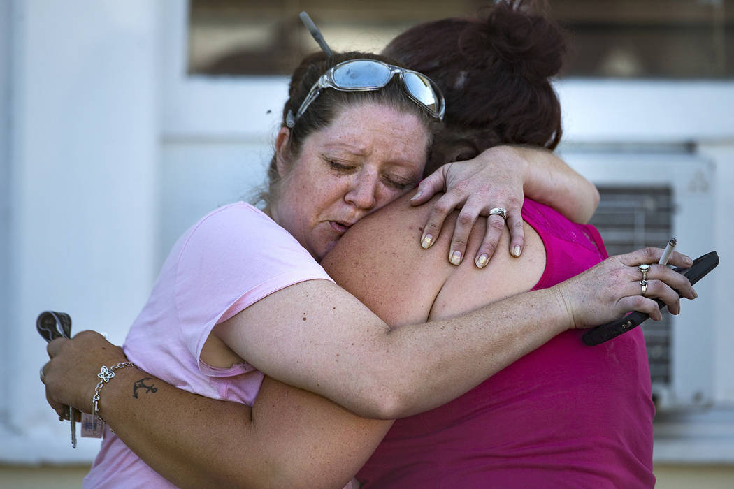 Carrie Matula embraces a woman after a fatal shooting at the First Baptist Church in Sutherland Springs, Texas, on Sunday, Nov. 5, 2017. Matula said she heard the shooting from the gas station whe ...