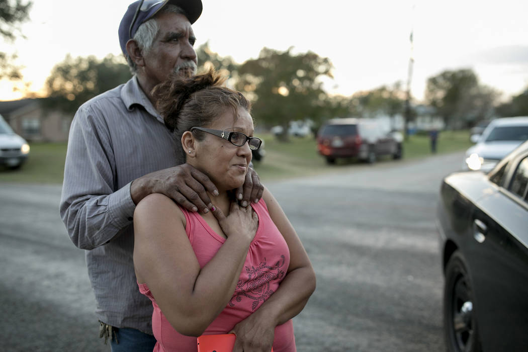 Enrique and Gabby Garcia watch investigators at the scene of a mass shooting at the First Baptist Church in Sutherland Springs, Texas, on Sunday Nov. 5, 2017. A man opened fire inside of the churc ...