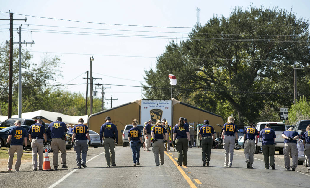 FBI agents search for evidence on a road near First Baptist Church in Sutherland Springs, Texas on Monday, Nov. 6, 2017. A man opened fire inside the church in the small South Texas community on S ...