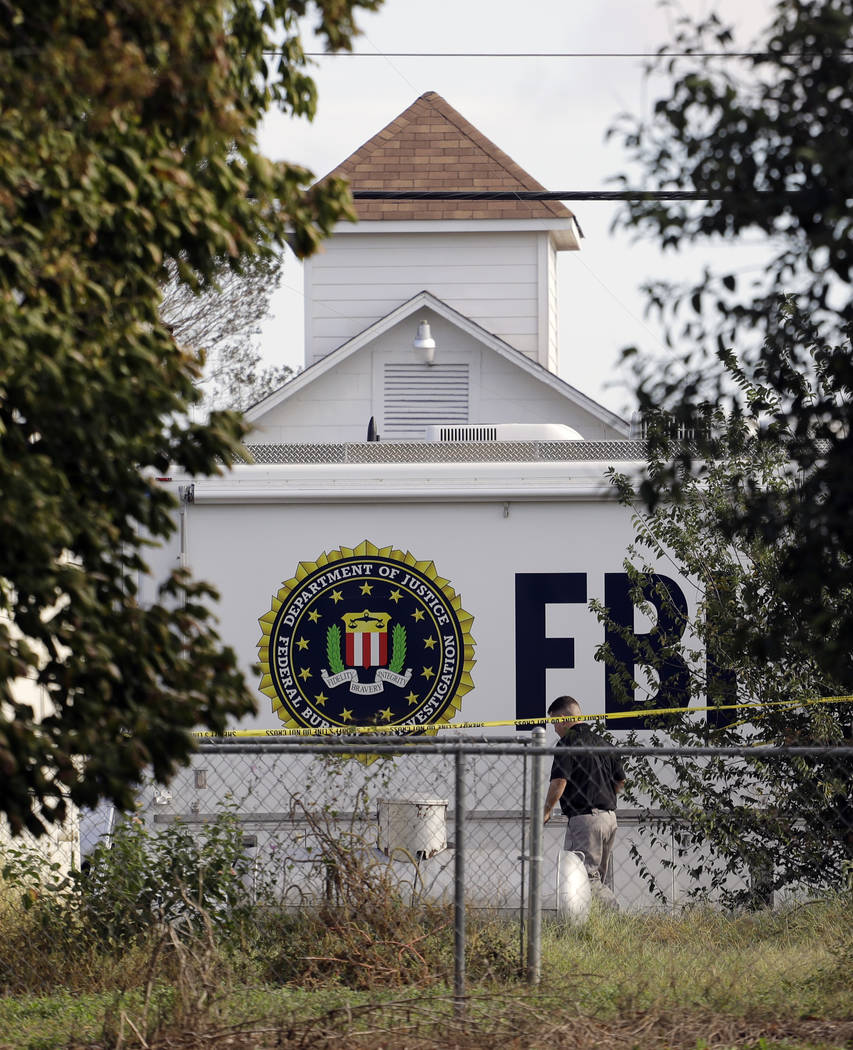 A law enforcement official investigates the scene of a shooting at the First Baptist Church of Sutherland Springs, Monday, Nov. 6, 2017, in Sutherland Springs, Texas. A man opened fire inside the  ...