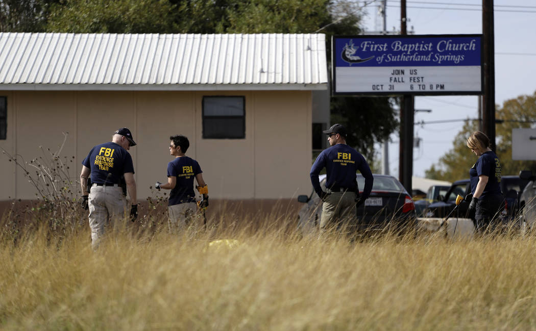 Law enforcement officials investigate the scene of a shooting at the First Baptist Church of Sutherland Springs, Monday, Nov. 6, 2017, in Sutherland Springs, Texas. A man opened fire inside the ch ...