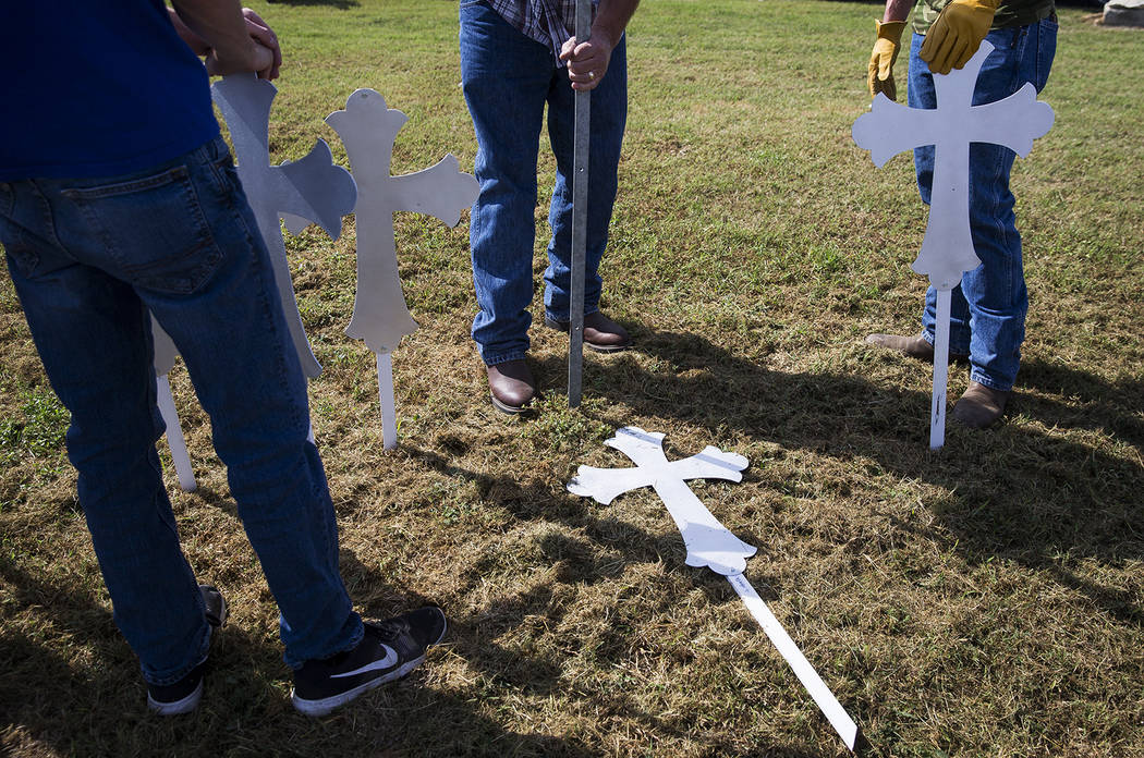 Doug John, center, drives a stake into the ground before erecting a cross in memory of one of the 26 people killed in Sutherland Springs, on Monday, Nov. 6, 2017. The shooting took place during a  ...