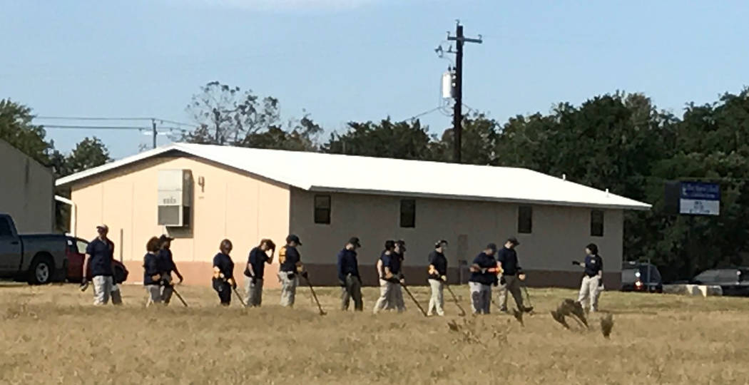 FBI agents use metal detectors in search evidence near church in Sutherland Springs, Texas. Photo by Gary Martin