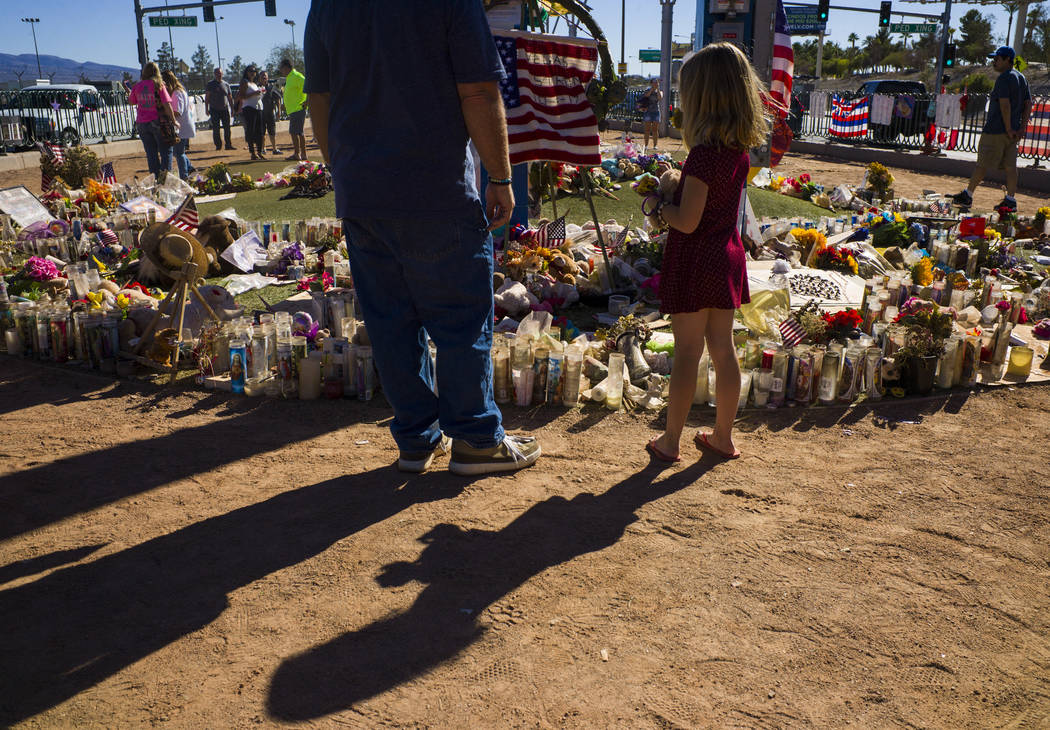 """Robert Patterson of Lomita, California, and daughter Brooke visit a makeshift memorial for the victims of the Oct. 1 shooting at a music festival, near the """"Welcome to Fabulous Las Vegas"""" sign in  ..."""