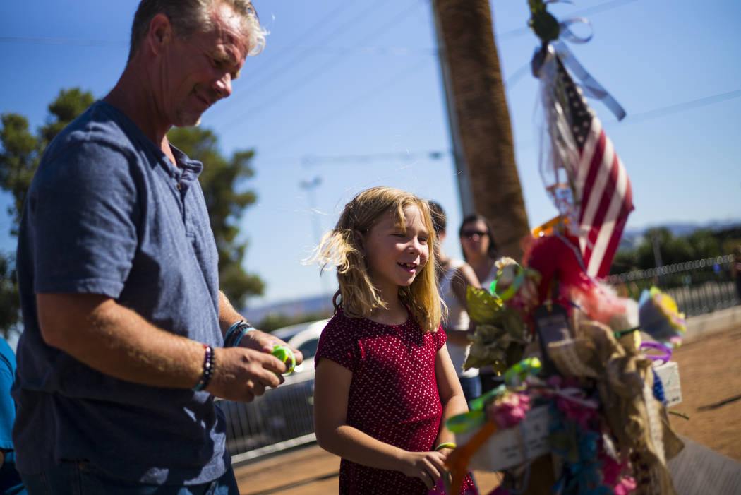 Robert Patterson, left, of Lomita, California, and daughter Brooke, 7, visit the makeshift memorial for Lisa Patterson, who was one of 58 people who died in the Oct. 1 shooting at a music festival ...