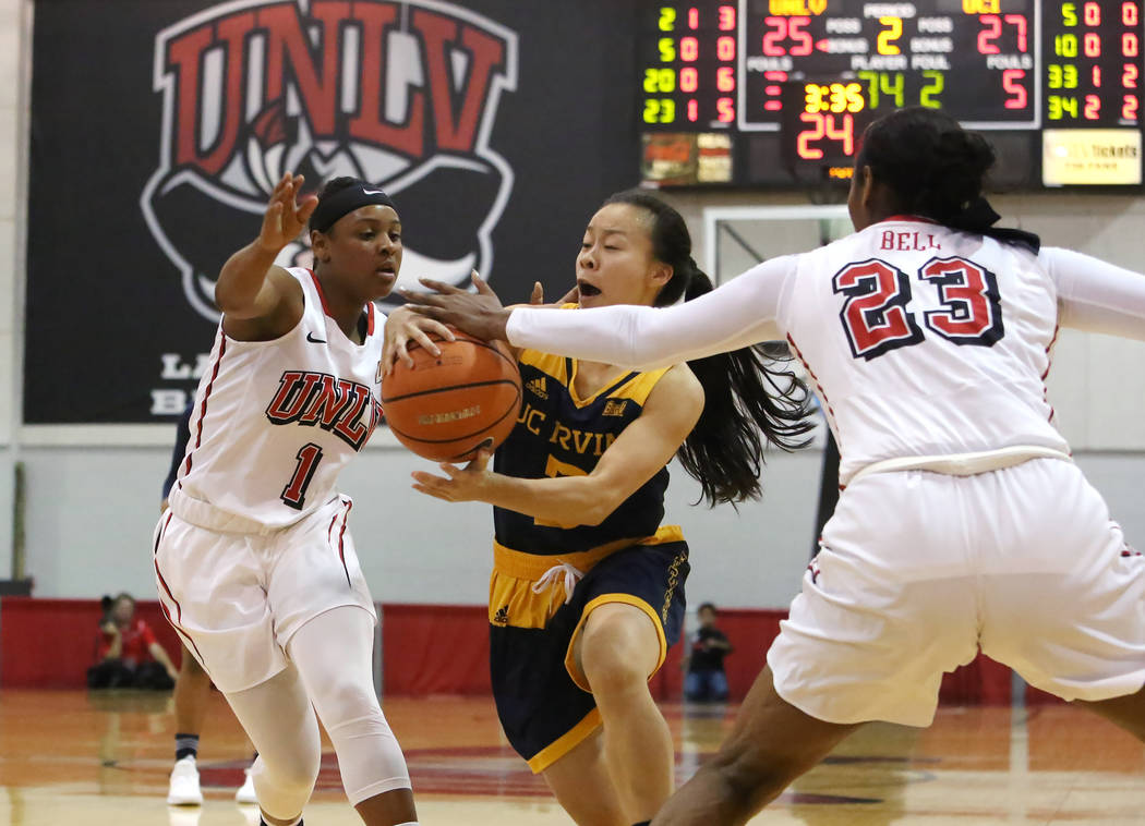 UNLV women's basketball guard Kavionnia Brown (1) and forward Jordyn Bell (23) defend UC Irvine's guard Lauren Saiki (3) during their game at the Cox Pavilion on Tuesday, Nov. 14, 2017, in Las Veg ...