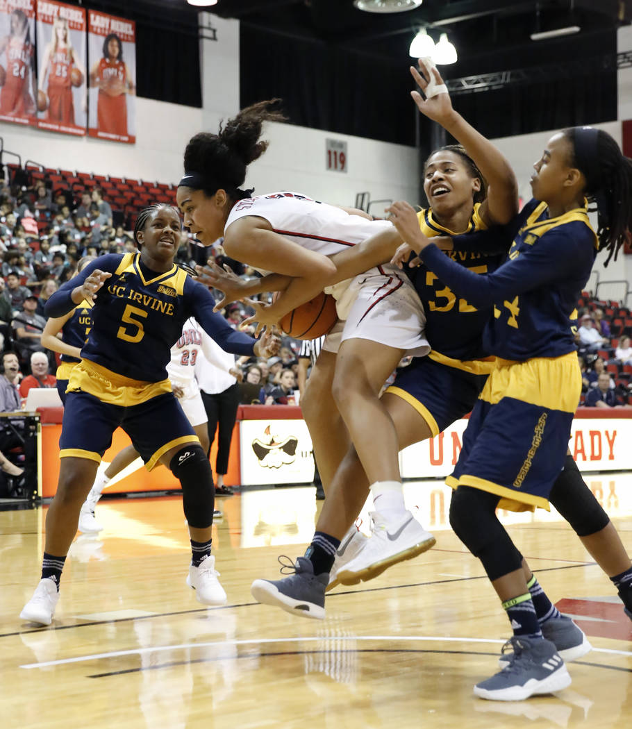 UNLV women's basketball forward/center Paris Strawther (3) fights for the ball against UC Irvine's Brooke Bayman (5), Deijah Blanks (35) and Yazzy Sa'Dullah (14) during their game at the Cox Pavil ...