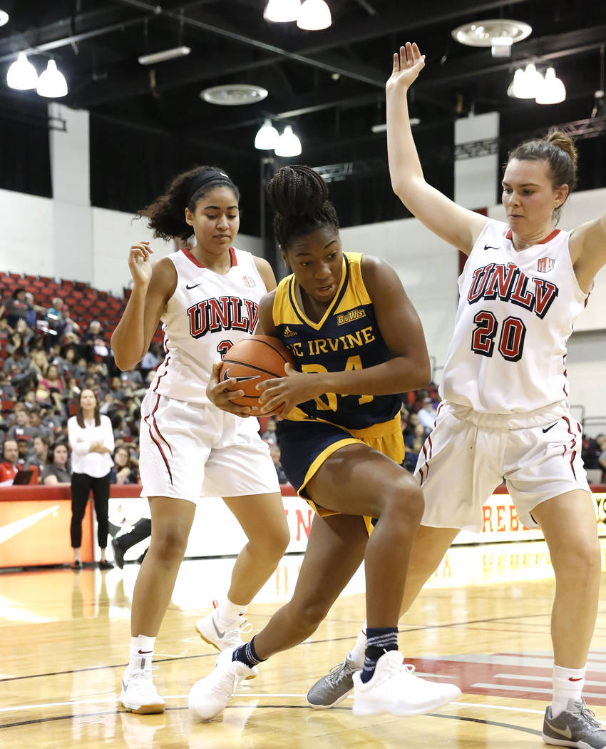 UC Irvine's guard forward Jordan Sanders (34) tries to drive past UNLV women's basketball forward Alyssa Anderson (20) during their game at the Cox Pavilion on Tuesday, Nov. 14, 2017, in Las Vegas ...