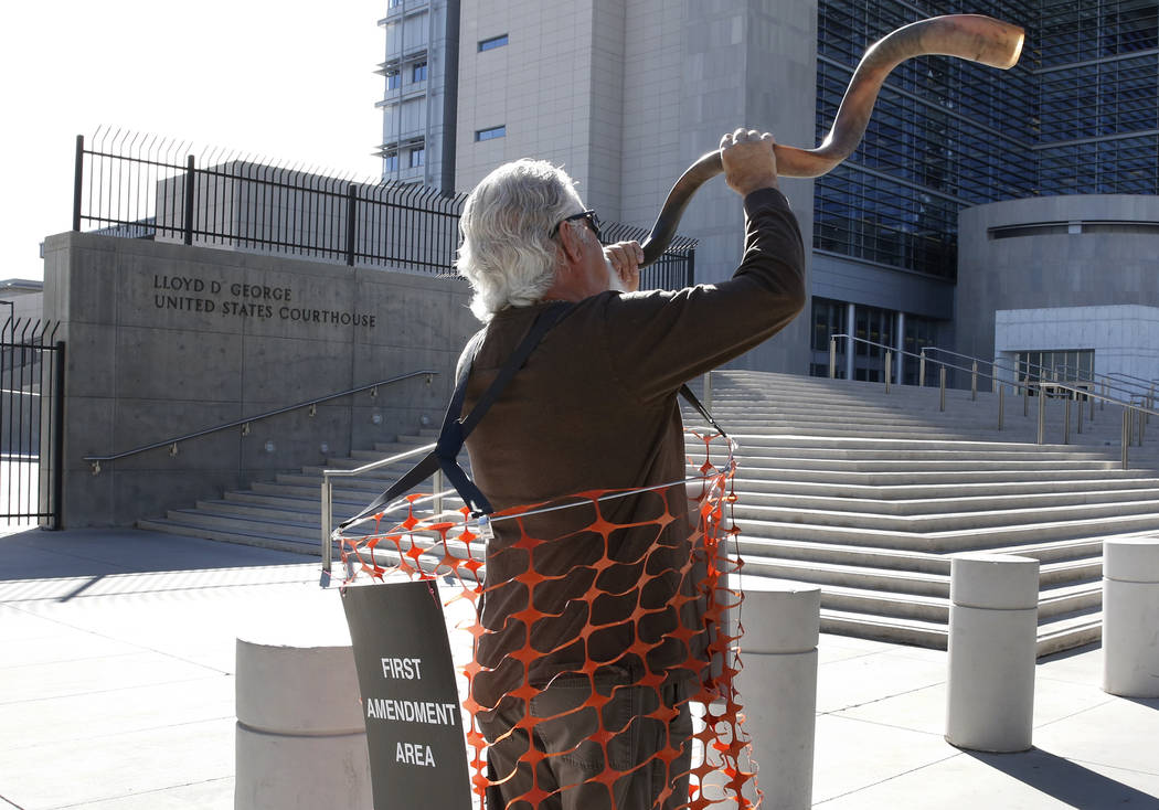 Brand Thornton blows a horn outside the Lloyd George U.S. Courthouse on Tuesday, Nov. 7, 2017 in support of Cliven Bundy's two sons and an independent militia man, who are on trial over the Bunker ...