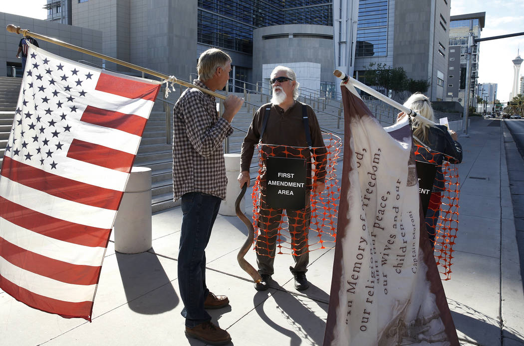 Jeff Banta, left, Brand Thornton, and Shawna Cox, right, protest outside the Lloyd George U.S. Courthouse on Tuesday, Nov. 7, 2017 in support of Cliven Bundy's two sons and an independent militia  ...