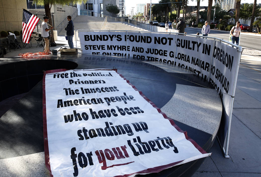 Bryce Poulsen, left, protests outside the Lloyd George U.S. Courthouse on Tuesday, Nov. 7, 2017 in support of Cliven Bundy's two sons and an independent militia man, who are on trial over the Bunk ...