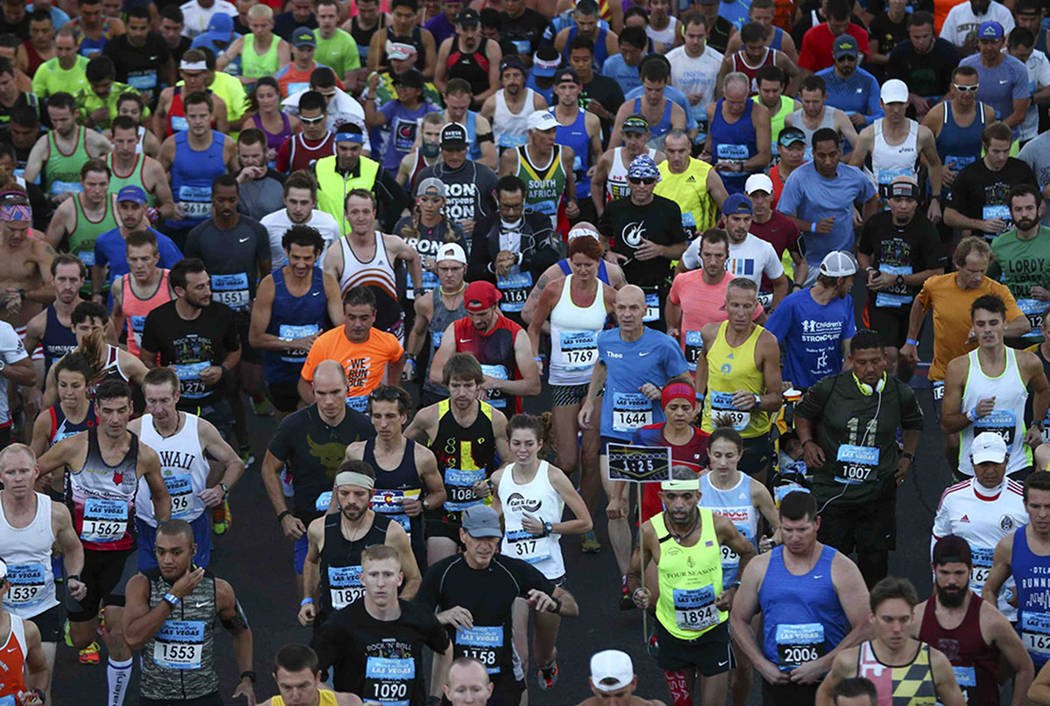 Race participants pass the start line during the Rock 'n' Roll Marathon in Las Vegas on Sunday, Nov. 13, 2016. (Chase Stevens/Las Vegas Review-Journal)