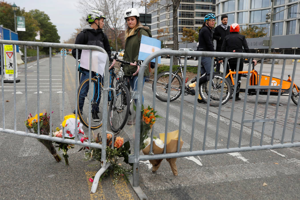 Amaya Lopez-Silvero, 20, and Elliot Levy, 21, look at a makeshift memorial for victims of Tuesday's attack outside a police barricade on the bike path next to West Street a day after a man driving ...