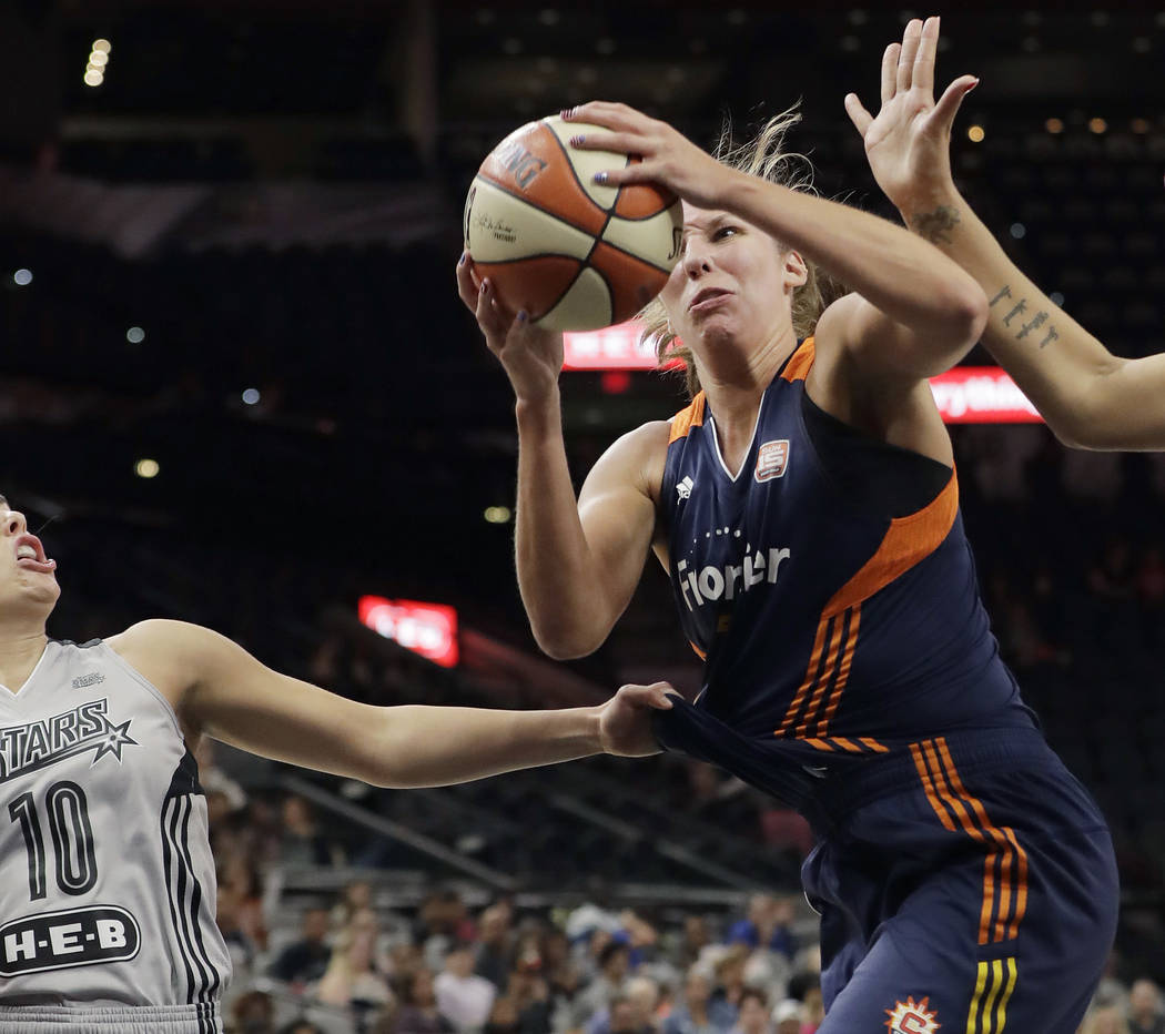 Connecticut Sun forward Kayla Pedersen, right, has her jersey grabbed by San Antonio Stars guard Kelsey Plum (10) as she tries to shoot during the first half of a WNBA basketball game, Wednesday,  ...