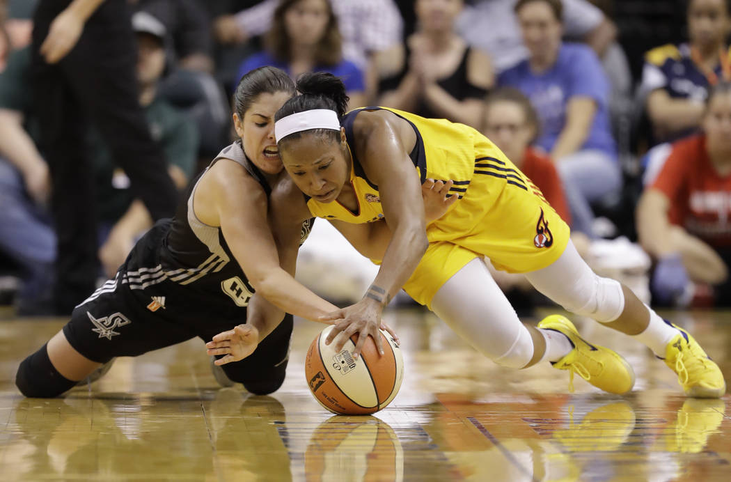 San Antonio Stars' Kelsey Plum, left, and Indiana Fever's Briann January dive for a loose ball during the second half of a WNBA basketball game, Wednesday, July 12, 2017, in Indianapolis. San Anto ...