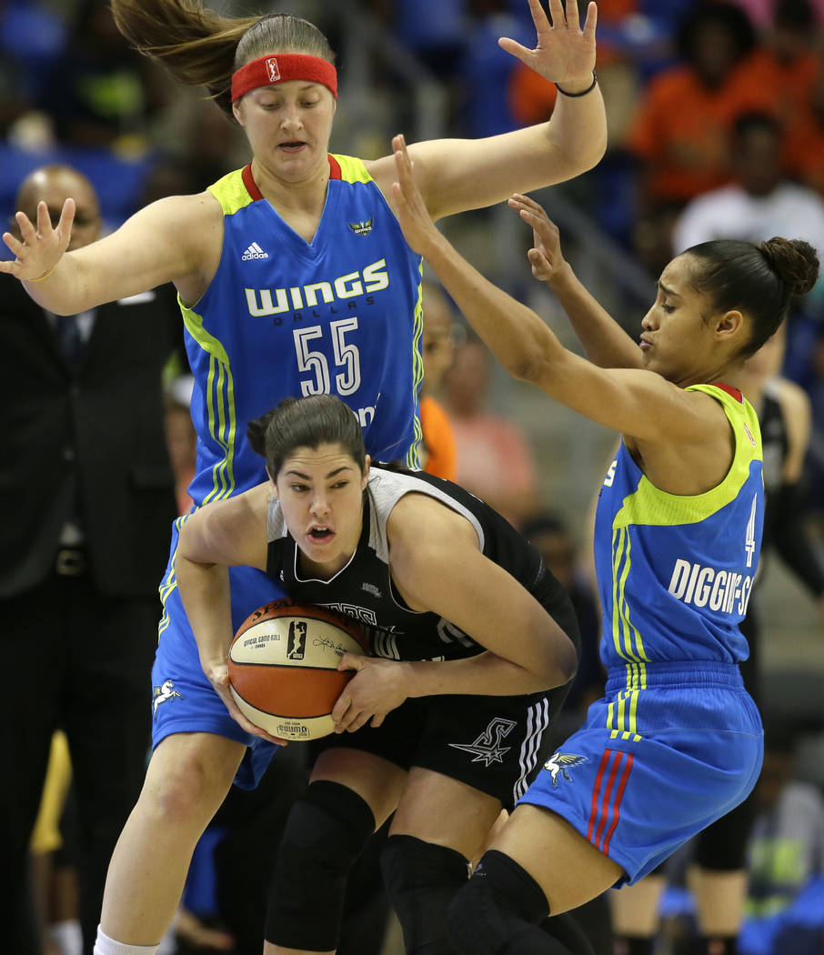 FILE - In this June 21, 2017, file photo, San Antonio Stars guard Kelsey Plum, center, tries the keep the ball from Dallas Wings defenders Theresa Plaisance (55) and Skylar Diggins-Smith (4) durin ...
