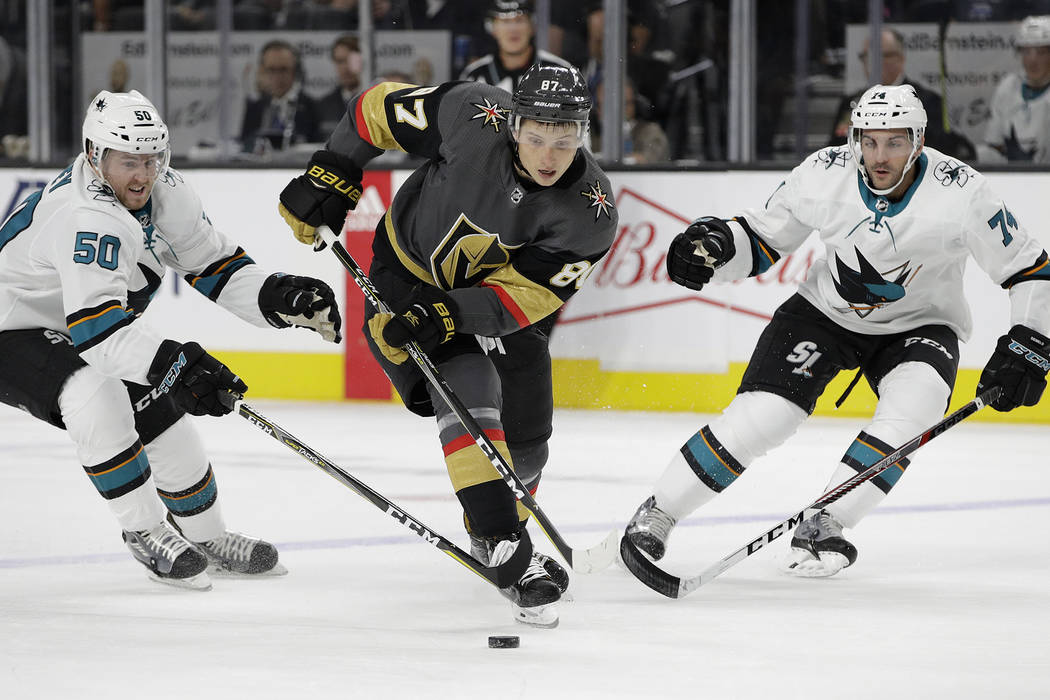 Vegas Golden Knights' Vadim Shipachyov, center, skates through San Jose Sharks' Chris Tierney, left, and defenseman Dylan DeMelo during the first period of an NHL preseason hockey game Sunday, Oct ...