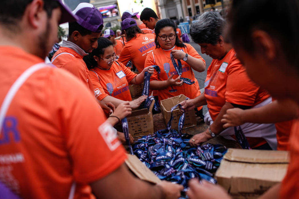 Charlene Gamayo, 16, of Las Vegas, third from right, assembles medals for runners in the Rock 'n' Roll Las Vegas Marathon along the Strip near The Mirage in Las Vegas, Sunday, Nov. 12, 2017. Joel  ...