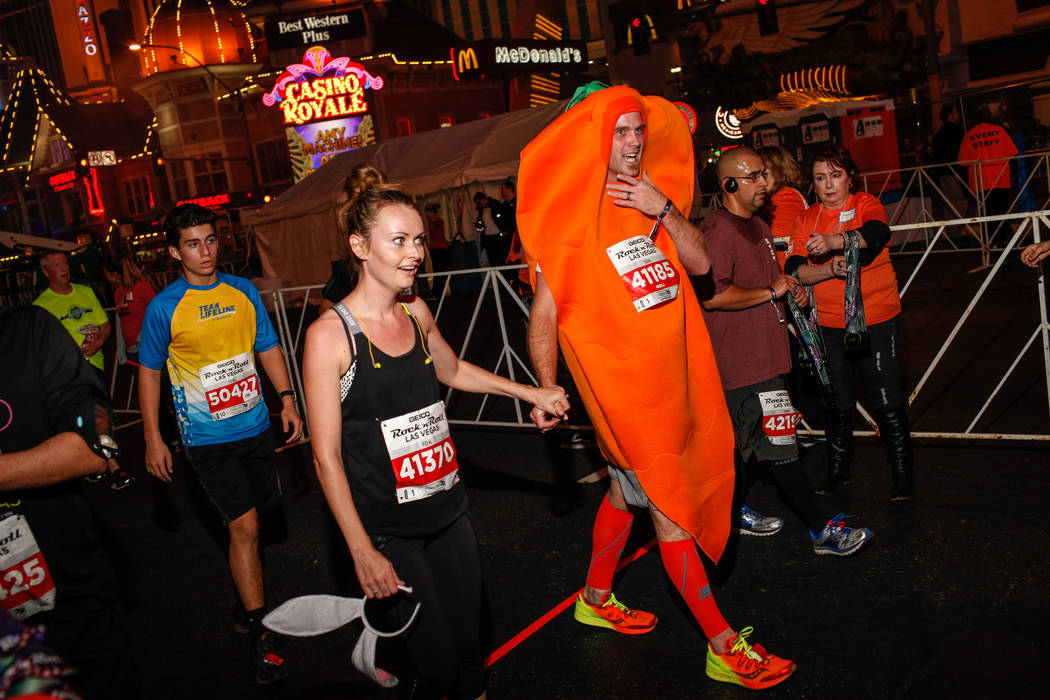 Jodi Jacobs, left, and Nathaniel Jacobs, right, both of Las Vegas cross the finish line at the 10K run of the Rock 'n' Roll Las Vegas Marathon along the Strip near The Mirage in Las Vegas, Sunday, ...