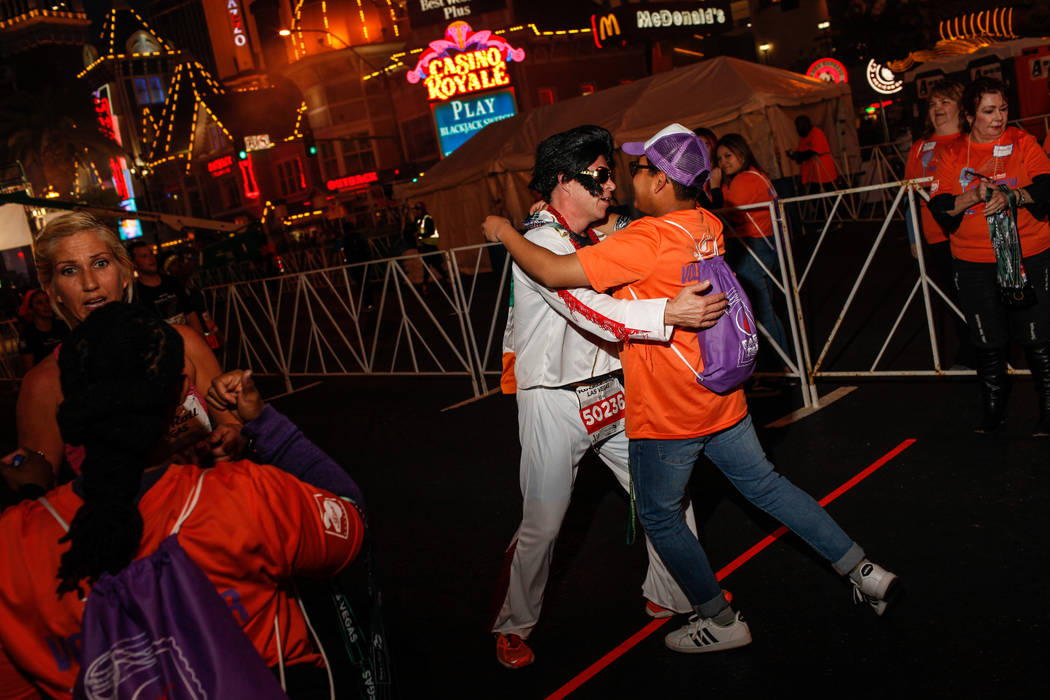 David Kiernan of Clogherhead, left, hugs Diego Simon of Las Vegas, right, after crossing the finish line at the 10K run of the Rock 'n' Roll Las Vegas Marathon along the Strip near The Mirage in L ...