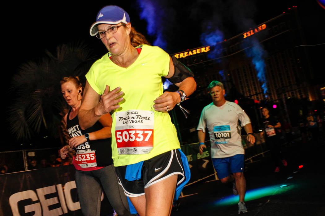 Cathy Hanehan of Saratoga Springs, center, crosses the finish line at the 10K run of the Rock 'n' Roll Las Vegas Marathon along the Strip near The Mirage in Las Vegas, Sunday, Nov. 12, 2017. Joel  ...
