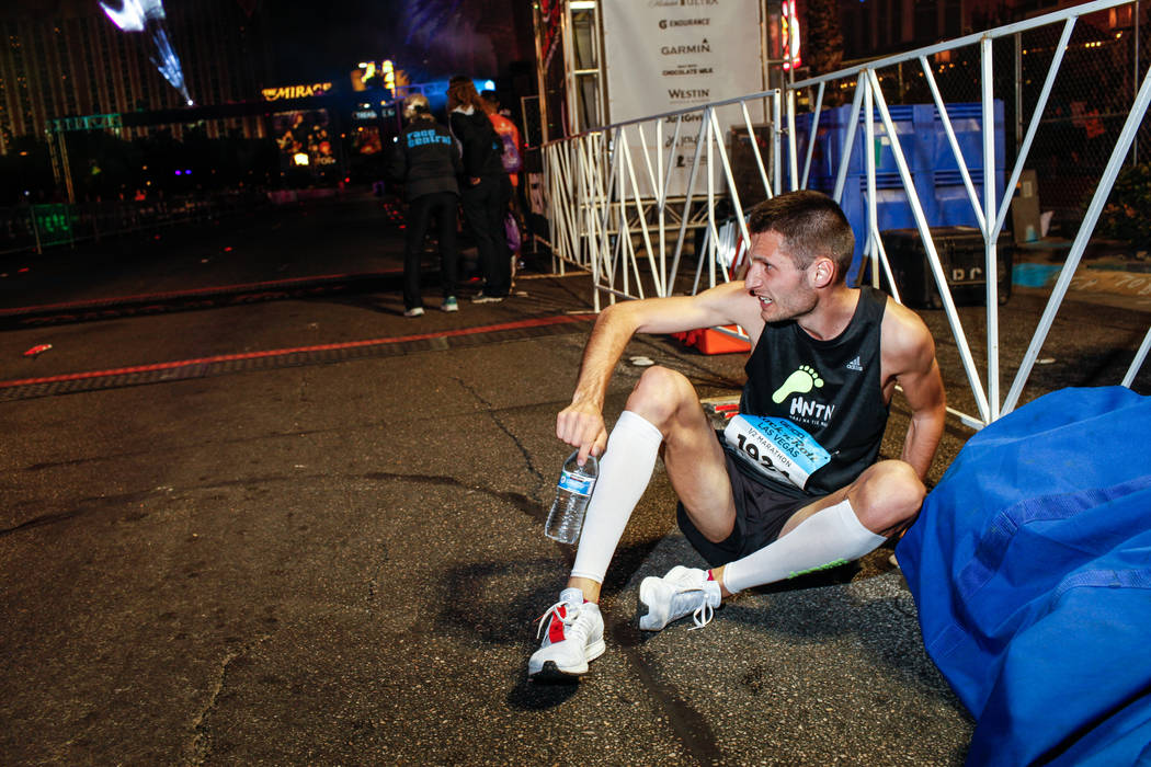 Marek Hladik of Bratislava catches his breath after crossing the finish line at the half marathon run of the Rock 'n' Roll Las Vegas Marathon along the Strip near The Mirage in Las Vegas, Sunday,  ...