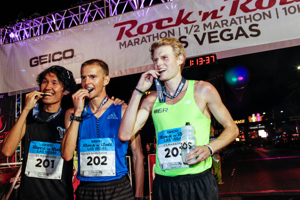 Second place winner Yuki Yagi of Japan, left, first place winner Jeffrey Eggleston of Boulder, center, and third place winner Wilkerson Given of the Woodlands, right, bite their medals after cross ...