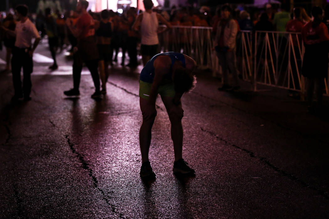 Mark Burgess of Buckhurst Hill catches his breath after crossing the finish line at the half marathon run of the Rock 'n' Roll Las Vegas Marathon along the Strip near The Mirage in Las Vegas, Sund ...