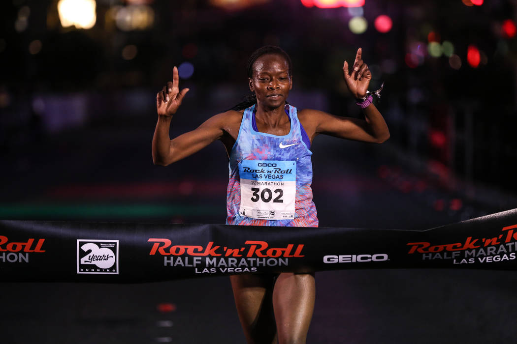 Janet Bawcom of Flagstaff crosses the finish line for first place at the women's half marathon run of the Rock 'n' Roll Las Vegas Marathon along the Strip near The Mirage in Las Vegas, Sunday, Nov ...