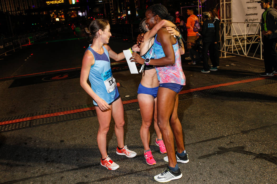 Second place winner Sarah Crouch, left, stands next to third place winner Georgia Porter, center, as she hugs first place winner Janet Bawcom, right, all of Flagstaff, after completing the women's ...
