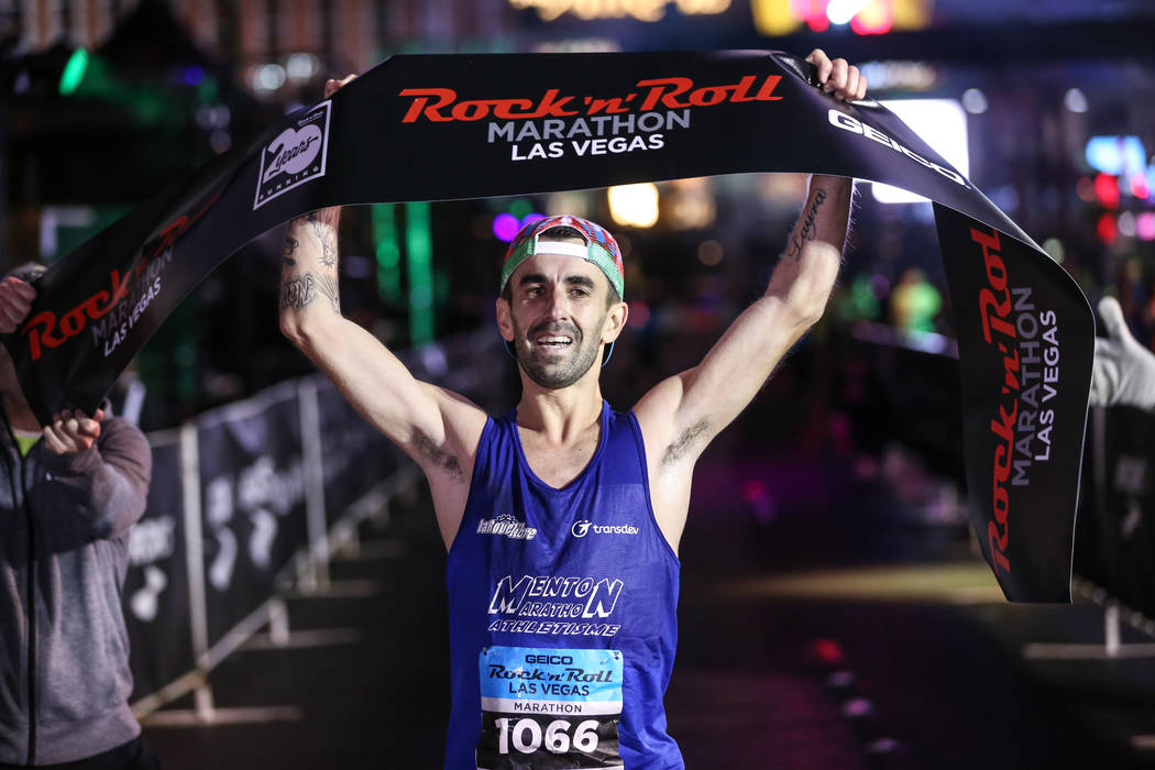 Gilles Rubio of Roquebrune Cap Martin, France, crosses the finish line winning first place at the men's marathon run of the Rock 'n' Roll Las Vegas Marathon along the Strip near The Mirage in Las  ...