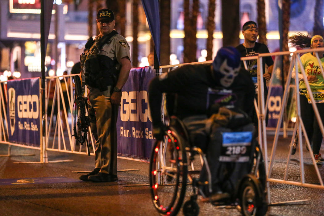 A police officer watches as a participant heads toward the finish line during the half marathon run of the Rock 'n' Roll Las Vegas Marathon along the Strip near The Mirage in Las Vegas, Sunday, No ...